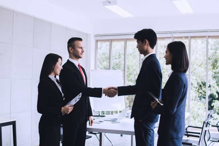 business interpreter shaking hands after successful meeting